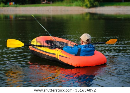Lonely young boy fishing from inflatable boat on lake early morning.