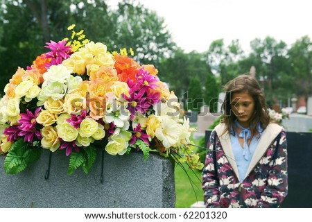 Lonely young girl visiting a grave with colored flowers at the cemetery - stock photo