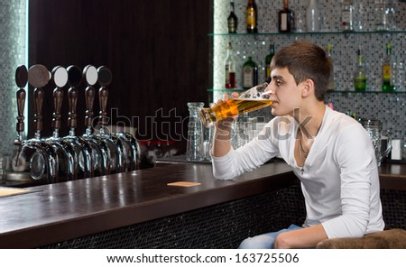 Lonely young man drinking alone at the pub sitting at the end of the bar counter sipping a pint of draught beer - stock photo