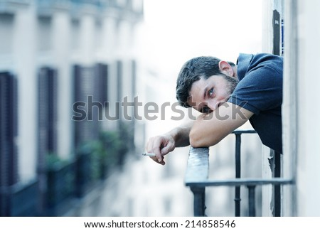 Lonely young man smoking outside at house balcony looking depressed, destroyed, sad and suffering emotional crisis and grief thinking of difficult and hard decision on an urban background - stock photo