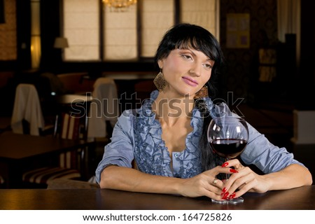 Lonely young woman drinking alone sitting at the bar counter with a large glass of red wine and a wistful dreamy expression - stock photo
