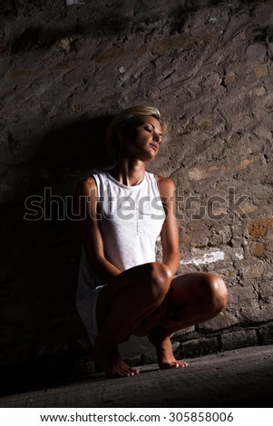 Lonely young woman sitting on the street, looking severely depressed. - stock photo