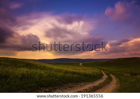 Lonesome road with blurry clouds - stock photo