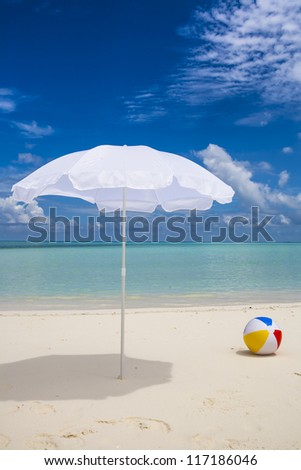 lonesome white sunshade and a ball at the beach with a blue sky and a turquoise sea - stock photo