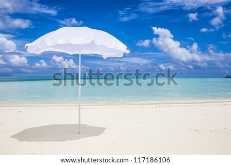 lonesome white sunshade at the beach with a blue sky and a turquoise sea