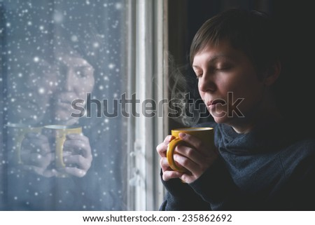 Lonesome woman drinking cup of coffee by the window of her living room while the snow is falling outside. Selective focus with shallow depth of field. - stock photo