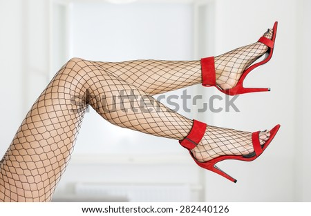 Long and sexy legs in elegant high heels and fishnet stockings - stock photo