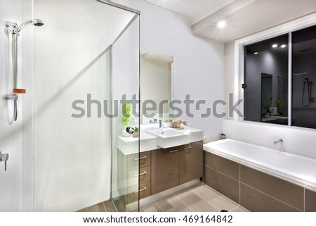 Long and white water tub over the window, a silver colored shower attached to the white wall. There are fancy pants with a wooden fish under the mirror and near to the sink with tap, the lights on