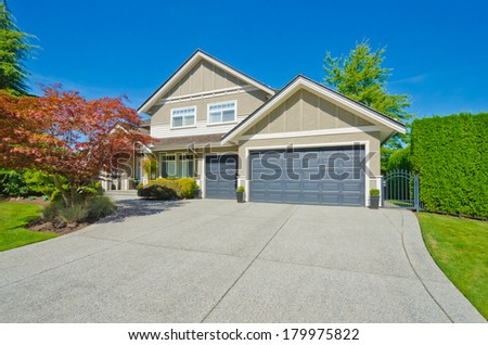 Long and wide driveway to the triple doors garage of the big custom made luxury house  in the suburbs of Vancouver, Canada. - stock photo