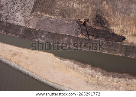 long arm excavator working on river bank in Poland - stock photo