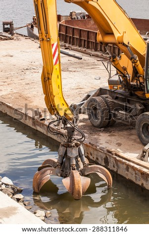 long arm excavator working on river bank in  Wroclaw Poland - stock photo