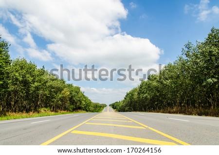 Long asphalt with the blue sky. - stock photo
