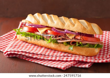 long baguette sandwich with ham cheese tomato and lettuce - stock photo