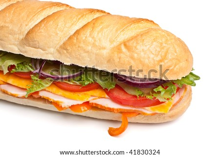 long baguette sandwich with lettuce, slices of fresh vegetables, ham, turkey breast and cheese - stock photo