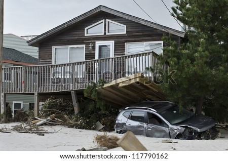 LONG BEACH ISLAND,NJ-NOVEMBER 1: A car is pinned under the deck of house after being swept away by the powerful storm surge caused by Hurricane Sandy in Holgate.Nov 1 2012, Long Beach Island, NJ - stock photo