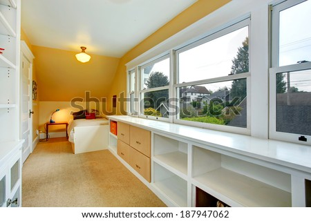 Long bedroom with vaulted ceiling and window. View of storage unit under the window and single bed - stock photo