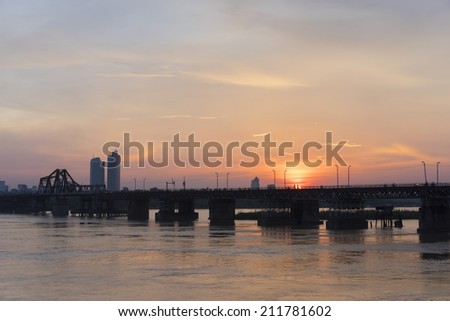 Long Bien bridge at sunset. Long Bien Bridge is a historic cantilever bridge across the Red River that connects two districts, Hoan Kiem and Long Bien