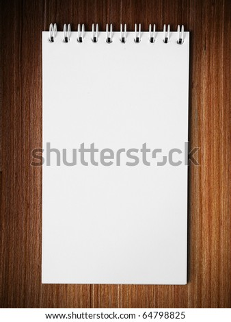Long blank white note book vertical on wood table background