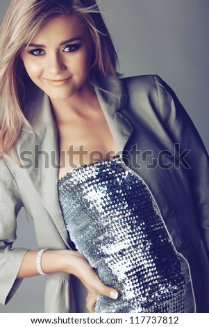 long blond hair beautiful woman in silver sequin dress on studio background - stock photo