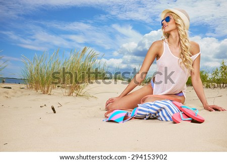 long blonde haired girl in bikini on  beach - stock photo