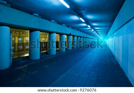 Long blue tunnel with light at the end. - stock photo