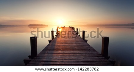 long boardwalk on the lake in the morning at sunrise, silent and light