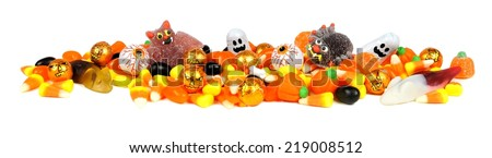Long border of assorted Halloween candy over white                    - stock photo