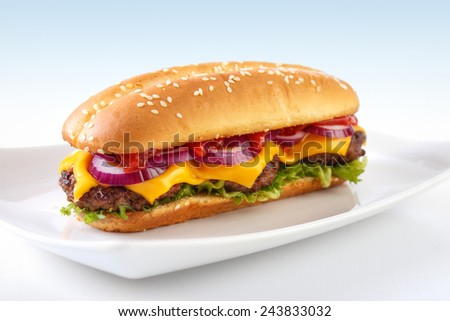 Long cheeseburger on plate , with three grilled patties , lettuce ,  red onion , cheddar cheese and ketchup - stock photo