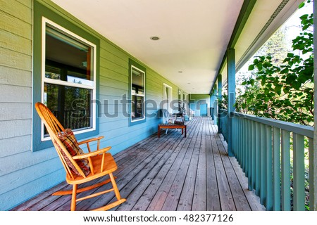 Long covered porch in turquoise color with rocking chair. Northwest, USA