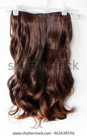 long curly brown wig on a white background