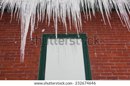 Long delicate fingers of ice hang from a gutter atop a red brick building with a green framed window reflecting the ice and snow. - stock photo