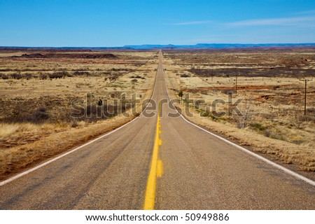 Long desert road stretching into the distance to the horizon. - stock photo