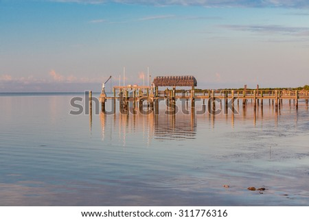 Long dock stretches out into deeper water in Key West, Florida. - stock photo