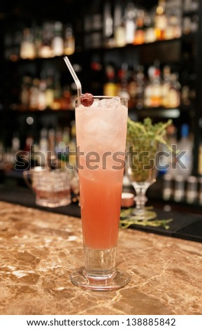 Long drink cocktail on bar counter with blurred bottles in background - stock photo