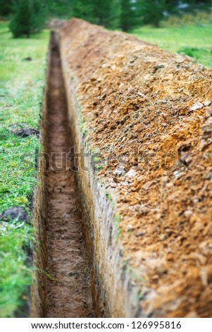 Long earthen trench dug to lay pipe. - stock photo