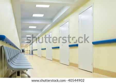 long empty yellow corridor with chairs in hospital - stock photo
