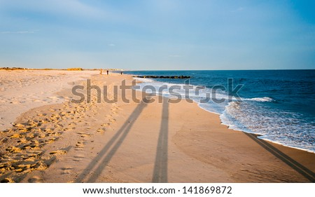 Long evening shadows on the beach at Cape May, New Jersey. - stock photo