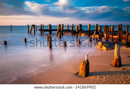 Long exposure at sunset of pier pilings in the Delaware Bay at Sunset Beach, Cape May, New Jersey. - stock photo