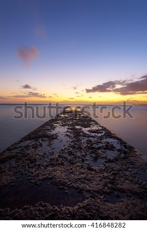 Long exposure at sunset of textured cement pier jutting out into Pacific Ocean from Waikiki Beach - stock photo