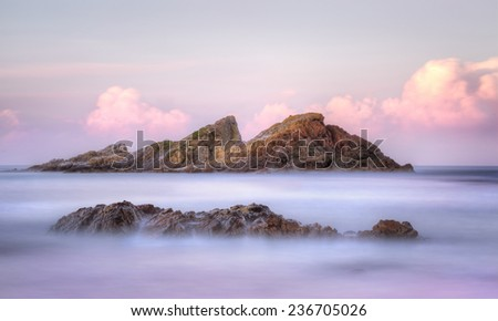 Long exposure ethereal sundown colours ocean flows and views to Statis Rock, at the eastern end of Sugarloaf Bay, Seal Rocks NSW Australia.   - stock photo