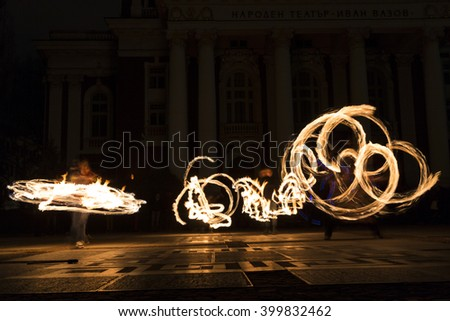 Long exposure image of an art performer at a fire show in the dark.