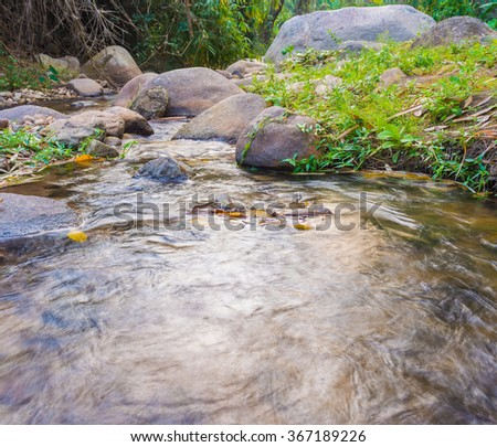 long exposure image of river and rock on day time. - stock photo