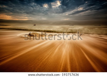 Long exposure landscape with stormy sea beach and waves flowing out