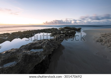 Long exposure of a beach on the north shore of Oahu, Hawaii during dusk. Tide pools in the foreground with sharp reflections atop and old reef. Flowing water along side the reef shelf.  - stock photo