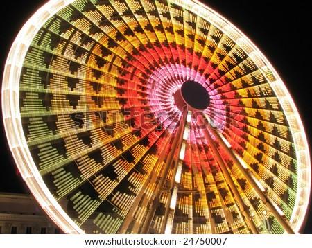 Long exposure of a Ferris Wheel ride at night - stock photo