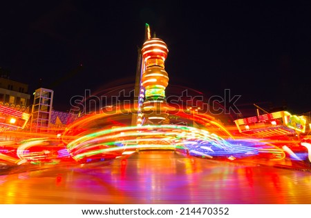 Long exposure of a funfair ride at night. - stock photo