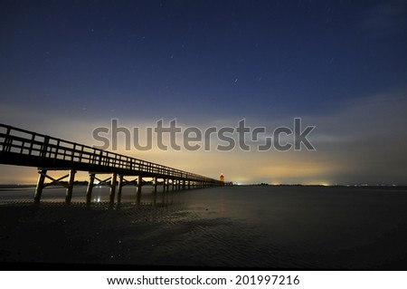 Long exposure of a pier at night  - stock photo