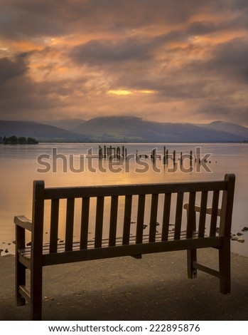 Long exposure of a Scottish loch and jetty. The mountains of the Trossachs surround the loch - stock photo