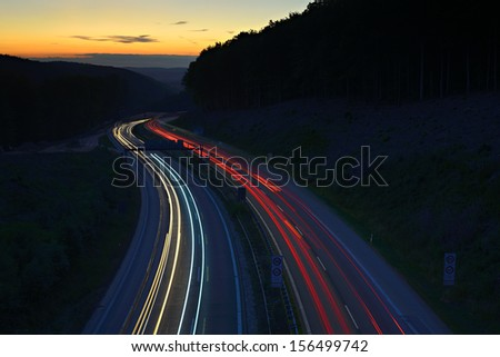 Long Exposure of Car Lights on Motorway at Sunset - stock photo