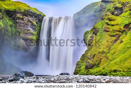Long exposure of famous Skogafoss waterfall in Iceland at dusk - stock photo